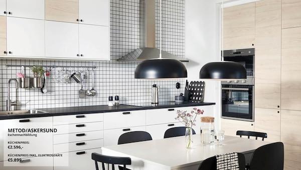 Eine Küche, u. a. mit dem METOD Wandschrank in Weiß, zwei schwarzen Hängeleuchten, einem Tisch und schwarzen Stühlen.
