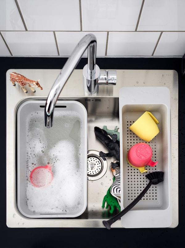 Eine Küchenspüle mit einer weissen GRUNDVATTNET Spülschüssel mit Spülwasser, in der Spielzeugtiere ein Bad nehmen.