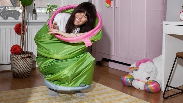 Eine lachende Person kauert in einem BUSA Spieltunnel versteckt in einem Kinderzimmer auf einem Teppich.