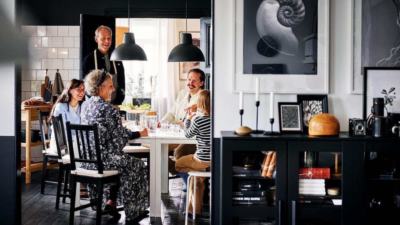 Eine lächelnde Familie sitzt in einem schwarz und weiß gestalteten Essbereich auf schwarzbraunen STEFAN Stühlen rund um zwei weiße MELLTORP Tische.
