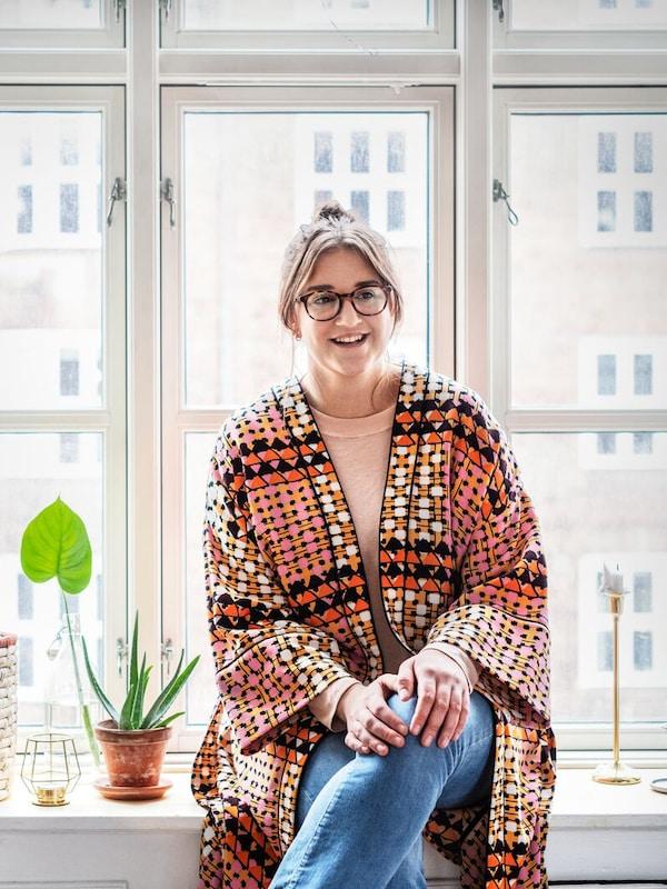 Eine lächelnde junge Person in einem farbenfrohen Kaftan sitzt auf einer Fensterbank in ihrer Wohnung.