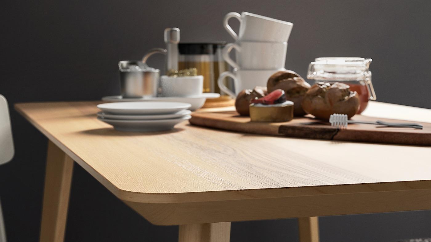 Eine LISABO Tischplatte aus Furnier, auf der Kaffeetassen, ein Schneidebrett mit einem Honigglas und ein paar Brötchen zu sehen sind.