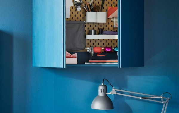 Eine Lochplatte an einer blauen Wand, mit blauen Regaltüren, darin Behälter, Scheren, Tacker & Stifte