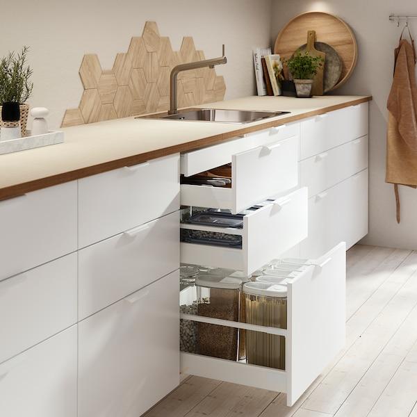 Eine moderne weiße Küche mit einer Arbeitsplatte aus Eiche, die mit offenen Schubladen mit Schubladenorganisation und Containern ausgestattet ist.