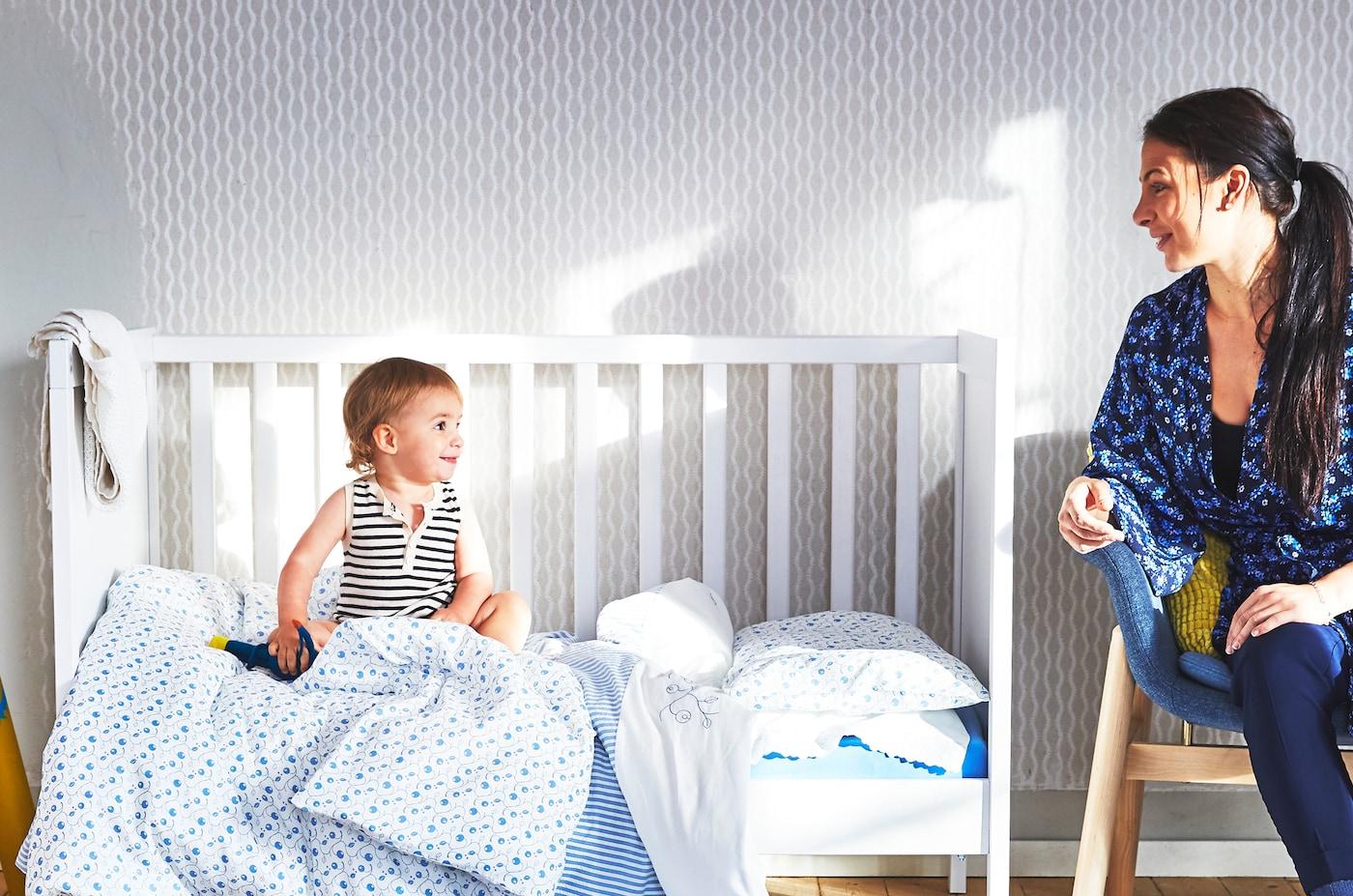 Eine Mutter sitzt auf einem Holzstuhl und ein Kleinkind in einem Babybett mit offener Seite. Die Bettwäsche ist in Blautönen gehalten. Mutter und Kind lächeln sich an.