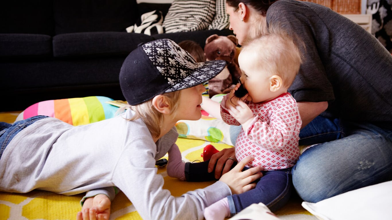 Eine Mutter spielt mit ihren drei Kindern im Wohnzimmer auf einem gelben Teppich