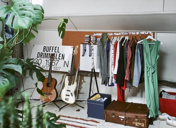 Eine offene Kleiderstange mit Kleidung neben Gitarren auf Ständern, einem Koffer und ein paar Fächern, u. a. mit SOMMARASTER Meterware weiss/bunt