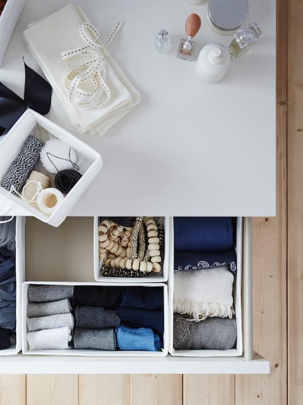 Eine offene Schublade im Schlafzimmer zeigt weisse SKUBB Boxen, in denen Ketten, gefaltete Socken und Schals zu sehen sind.