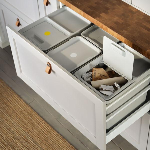 Eine offene Schublade mit diversen Mülleimern zur richtigen Mülltrennung und Sortierung.