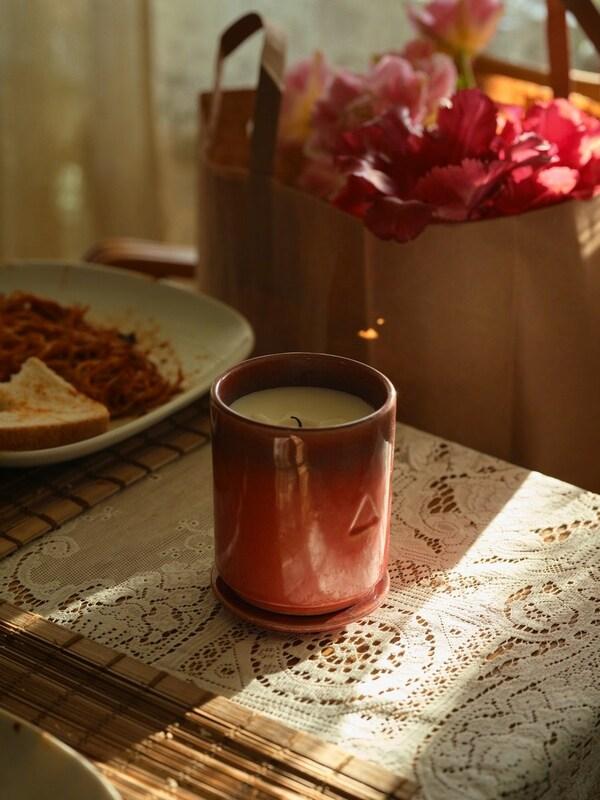 Eine OSYNLIG Duftkerze mit Rosen und Himbeerduft steht in einem Kerzenhalter auf einem Tisch. Dahinter ist eine Papiertüte mit Blumen zu sehen. Daneben ein Teller mit Essensresten.
