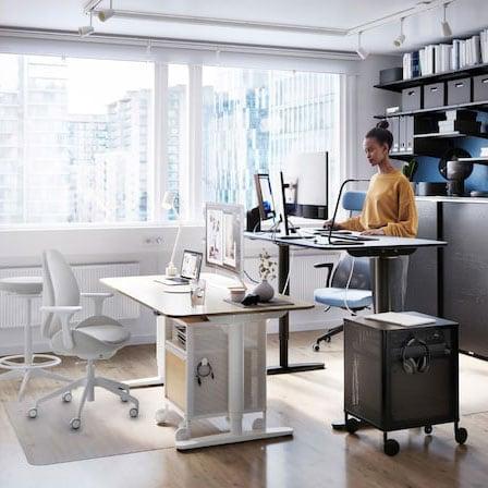 Eine Person arbeitet an einem BEKANT Sitz-/Stehschreibtisch neben einem grossen Fenster. An der Wand dahinter stehen viele Aktenordner in einer ALGOT Regalkombination.