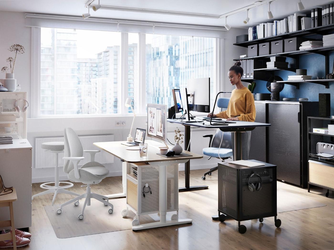 Eine Person arbeitet an einem BEKANT Sitz-/Stehschreibtisch neben einem großen Fenster. An der Wand dahinter stehen viele Aktenordner in einer ALGOT Regalkombination.