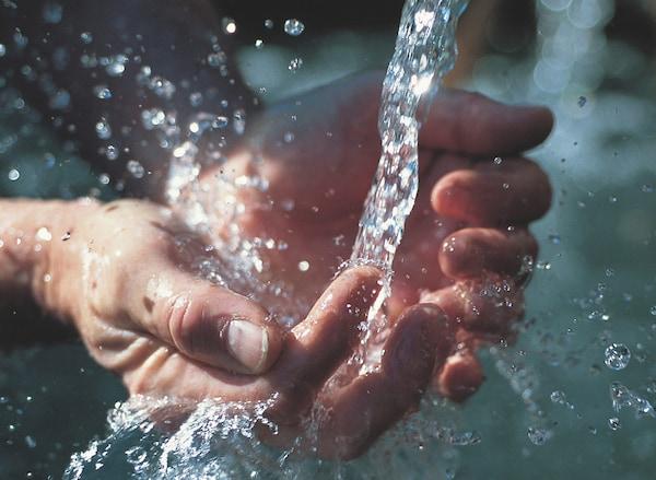 Eine Person fängt das Wasser aus einer Mischbatterie mit den Händen auf.