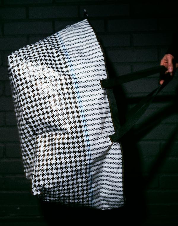 Eine Person hält die SAMMANKOPPLA Tasche in einem dunklen Raum. Ihre glänzende Oberfläche und das Karomuster sind im Kamerablitzlicht zu sehen.