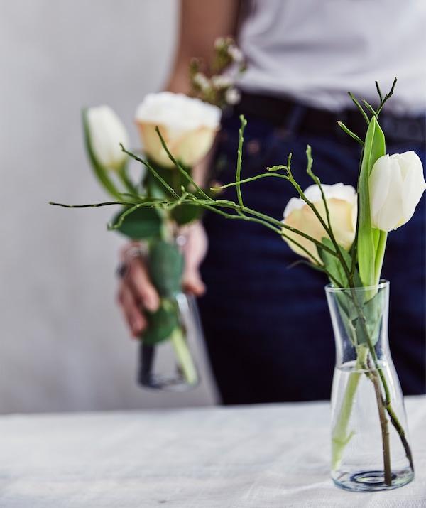 Eine Person hält TIDVATTEN Vase aus Klarglas mit Blumen gefüllt in den Händen. Auf dem Tisch davor ist eine weitere Vase zu sehen.