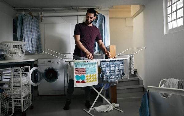 Eine Person hängt Wäsche an MULIG Wäschetrockner im Waschraum auf.