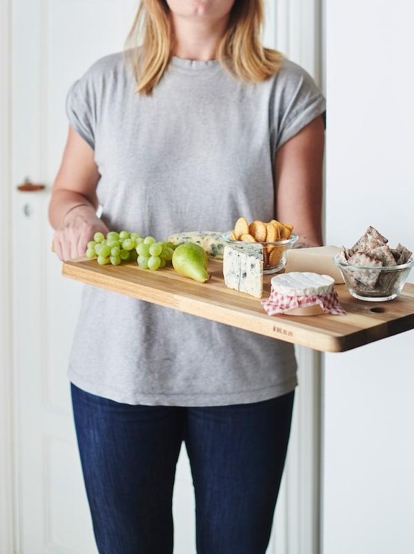 Eine Person in Jeans und T-Shirt, die ein SMÅÄTA Schneidebrett mit Käse und Obst in Händen hält.