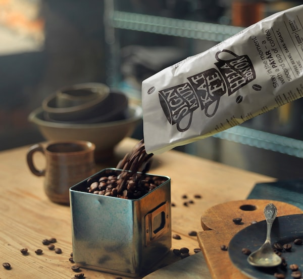 Eine Person kippt Kaffeebohnen aus einem Sack