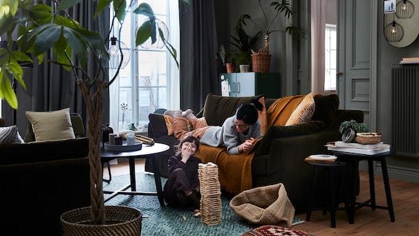 Eine Person liegt auf einem FÄRLÖV Sofa und schaut ihrem Kind zu, das auf dem Boden davor spielt. An der Zimmerdecke hängen GRINDFALLET Hängeleuchten in Schwarz.