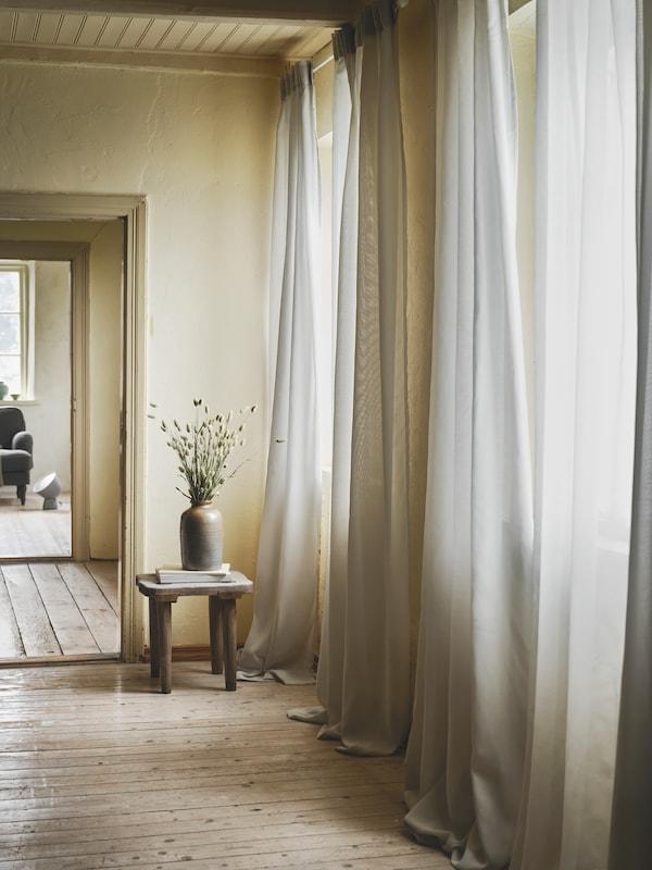 Eine Person liegt schlafend auf einem VINLIDEN Sofa in der Mitte eines grossen Raumes. Hinter dem Sofa hängt eine lange, rosafarbene Gardine.