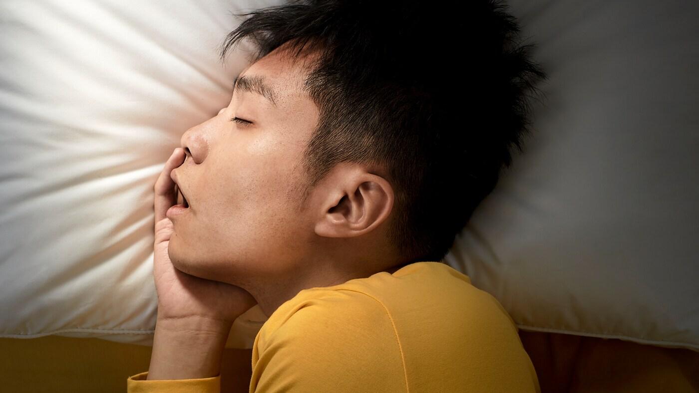 Eine Person mit einem gelben Oberteil schläft auf der Seite. Der Kopf liegt auf einem ergonomischen PRAKTVÄDD Kissen mit einem weißen Bezug.