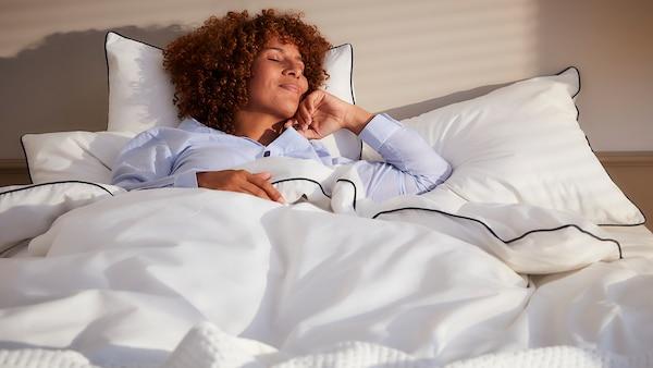 Eine Person mit Locken liegt lächelnd auf einem Bett mit drei Kopfkissen in weißen Bezügen und einer weißen Bettdecke.