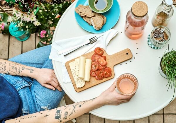 Eine Person mit tätowierten Armen sitzt an einem runden, cremefarbenen Tisch und hält ein Glas in der Hand. Auf dem Tisch steht ein Teller mit Käse und Tomaten.