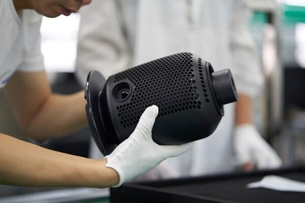 Eine Person mit weißen Handschuhen hält in einer Fabrik den Fuß einer schwarzen SYMFONISK Tischleuchte mit WiFi-Speaker