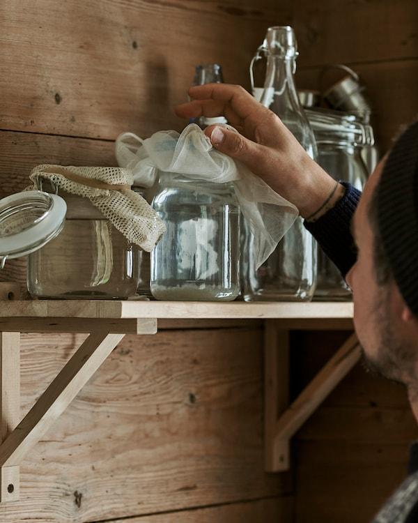 Eine Person nimmt ein Einmachglas von einem Regal, das auf einer EKBY VALTER Konsole ruht.