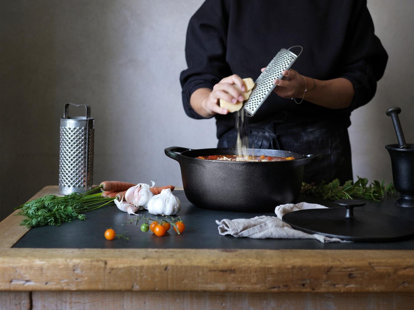 Eine Person reibt über einem schwarzen VARDAGEN Kochgeschirr etwas in eine Suppe.