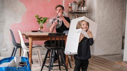 Eine Person sitzt an einem Esstisch und montiert eine Leuchte, während ein Kind mit der Pappverpackung spielt.