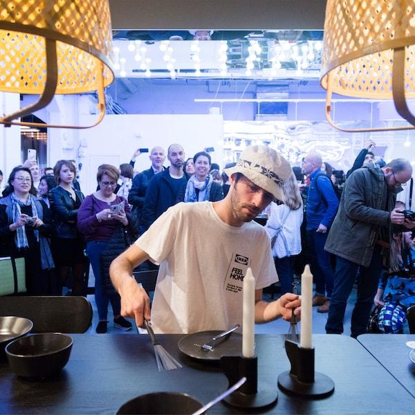 Eine Person spielt auf Geschirr wie auf einem Schlagzeug, während ein Publikum interessiert zuschaut.
