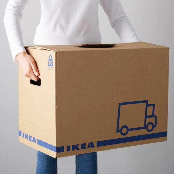 Eine Person trägt einen IKEA JÄTTENE Umzugskarton