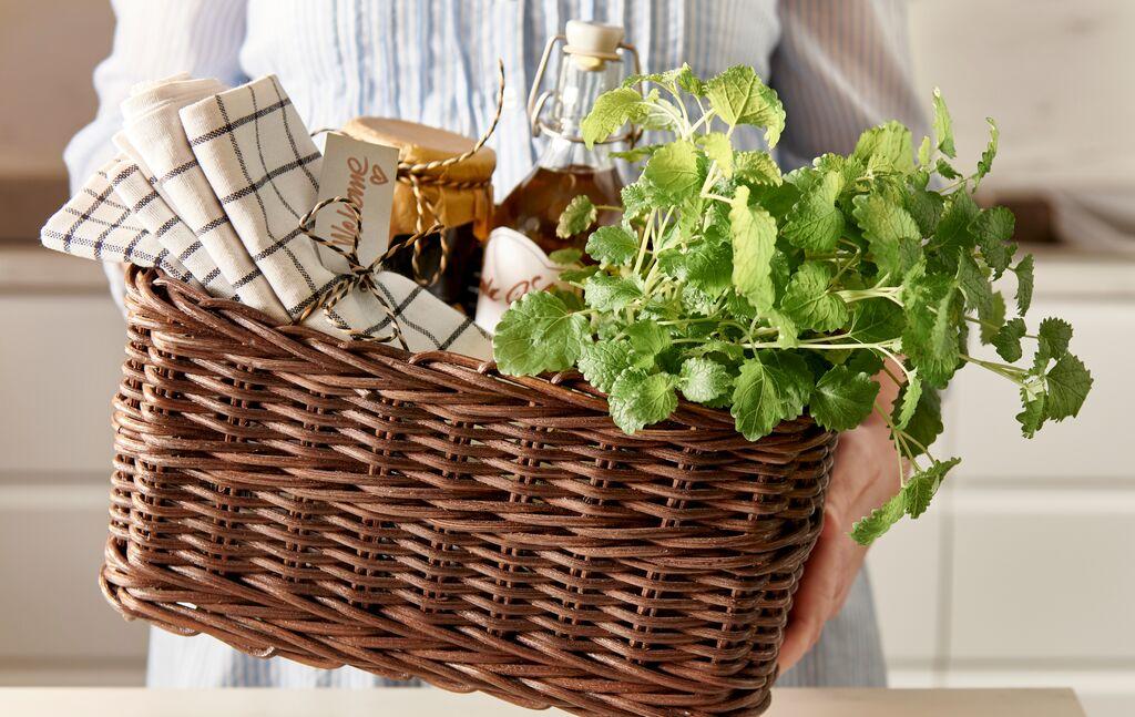 Eine Person überreicht einen GABBIG Korb, der mit karierten Geschirrtüchern, selbst gemachten Konfitüren in Glasbehältern und frischen Kräutern gefüllt ist.