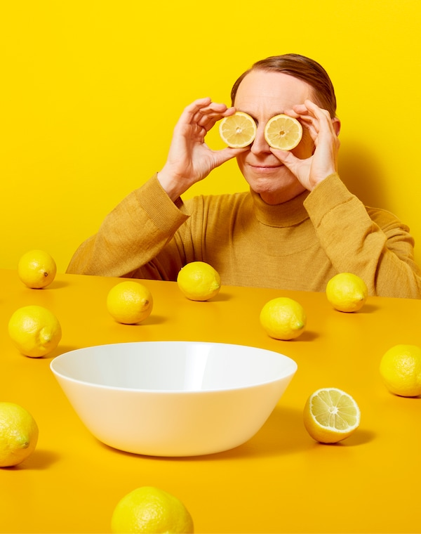 Eine Person vor einer gelben Wand in einem gelben Pullover hält sich zwei Zitronenhälften vor die Augen.
