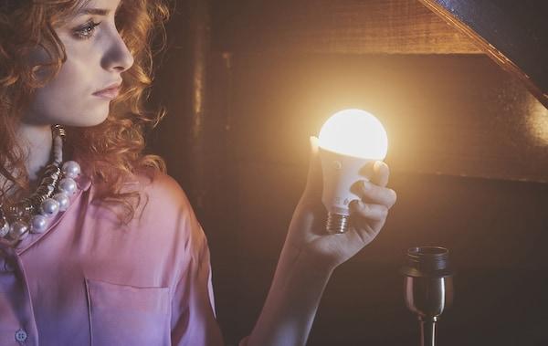 Eine rothaarige Frau hält in einem holzverschalten Raum ein leuchtendes Leuchtmittel in der Hand.