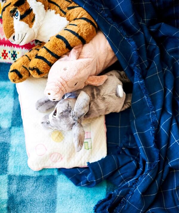 Eine Sammlung verschiedener Stofftiere auf einem blauen Teppich, u. a. DJUNGELSKOG Stofftier Tiger.