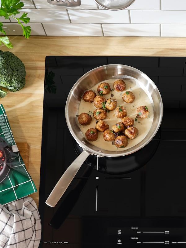 Eine Sautépfanne mit Fleischbällchen in Soße steht auf einem Induktionskochfeld.