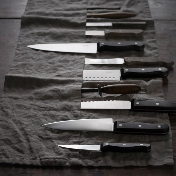 Eine schwarze Messerrolle mit etwa 10 Messern darin. Einige von ihnen stecken in ihren Taschen, andere liegen obenauf.