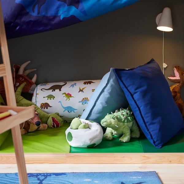 Eine selbst gebaute Höhle aus einer klappbaren Gymnastikmatte, aus der ein JÄTTELIK Stofftier hervorschaut.