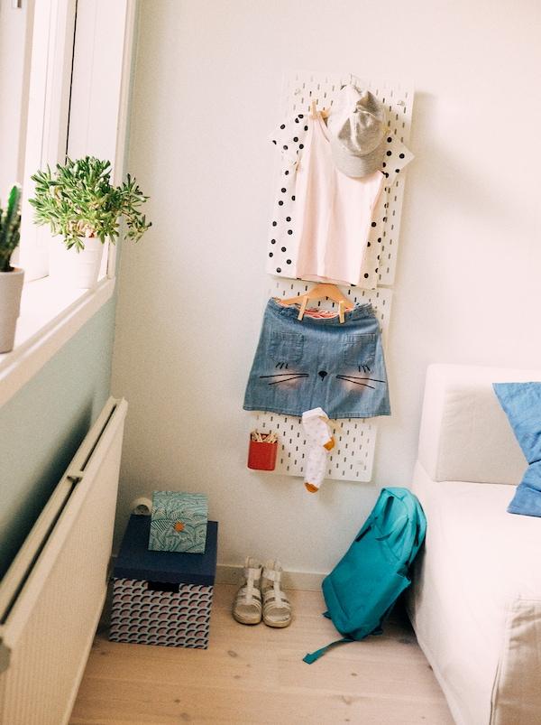 Eine SKÅDIS Lochplatte hält hier ein komplettes Schuloutfit bereit für den nächsten Tag – bis hin zu Socken, Schultasche und Schuhen.