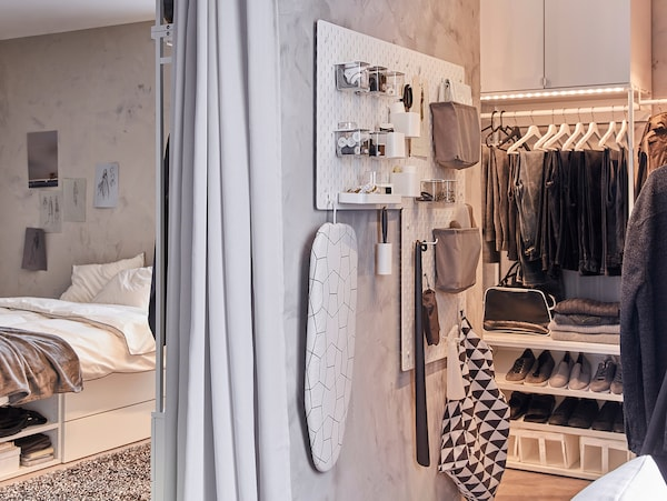 Eine SKÅDIS Lochplatte ist hier bestückt mit Utensilien rund um Kleiderpflege und Accessoires.