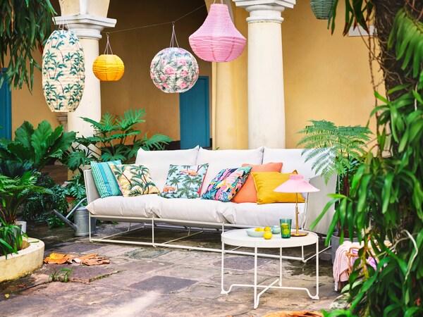 Eine sommerliche Terrasse mit einem Loungesofa einem Cafetisch und vielen Pflanzen, dekoriert mit Lampions