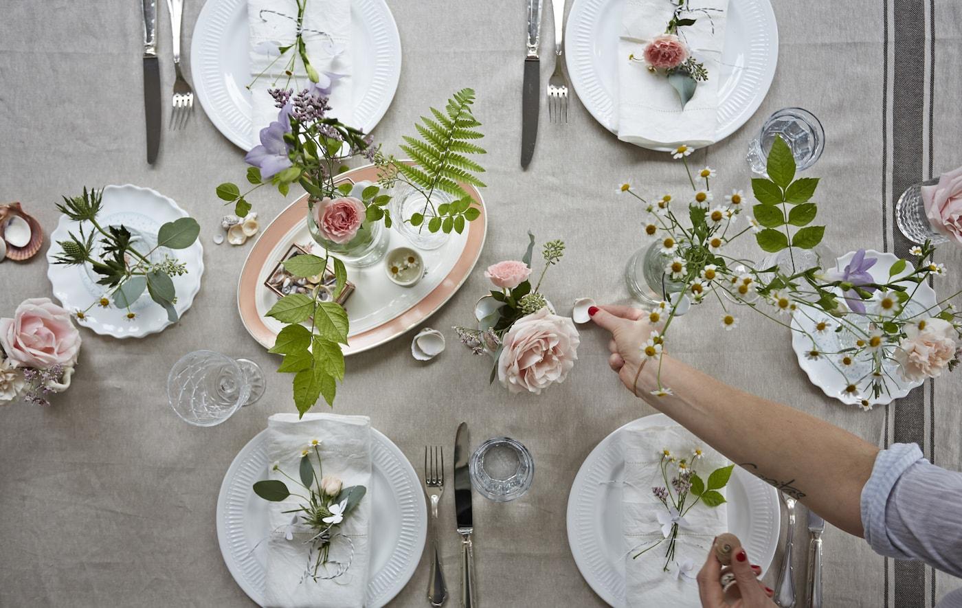 Eine Sommertafel mit frischen Blumen, Sträuchern weißen Tellern & Edelstahl-Besteck