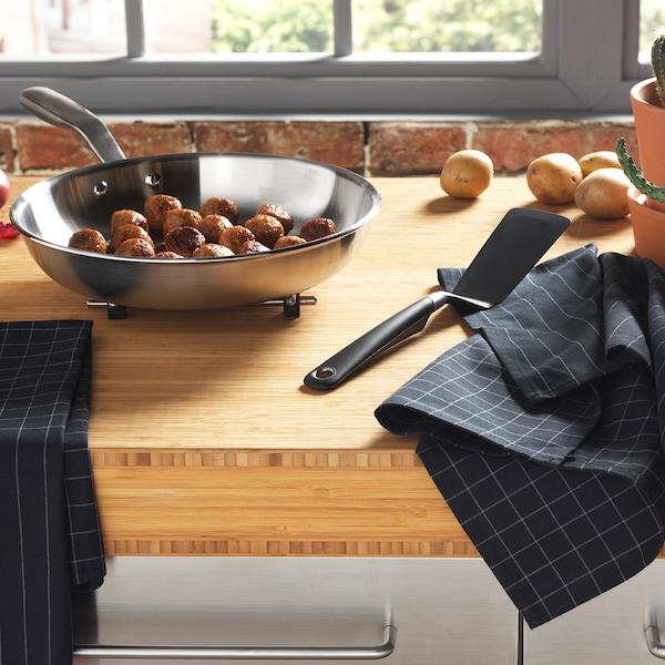 Eine Stahlpfanne mit Fleischbällchen darin, auf einer Küchentheke.