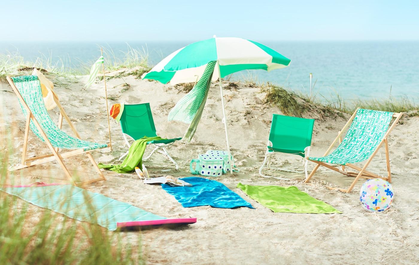 Eine Szene am Strand mit Sonnenschirm, leichten Liegestühlen & Strandmatten in türkis-grünen Farben