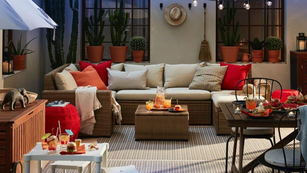 Eine Terrasse mit Sofa, einem kleineren weißen Tisch und Hockern. Daneben sind ein Esstisch und ein Sonnenschirm zu sehen.