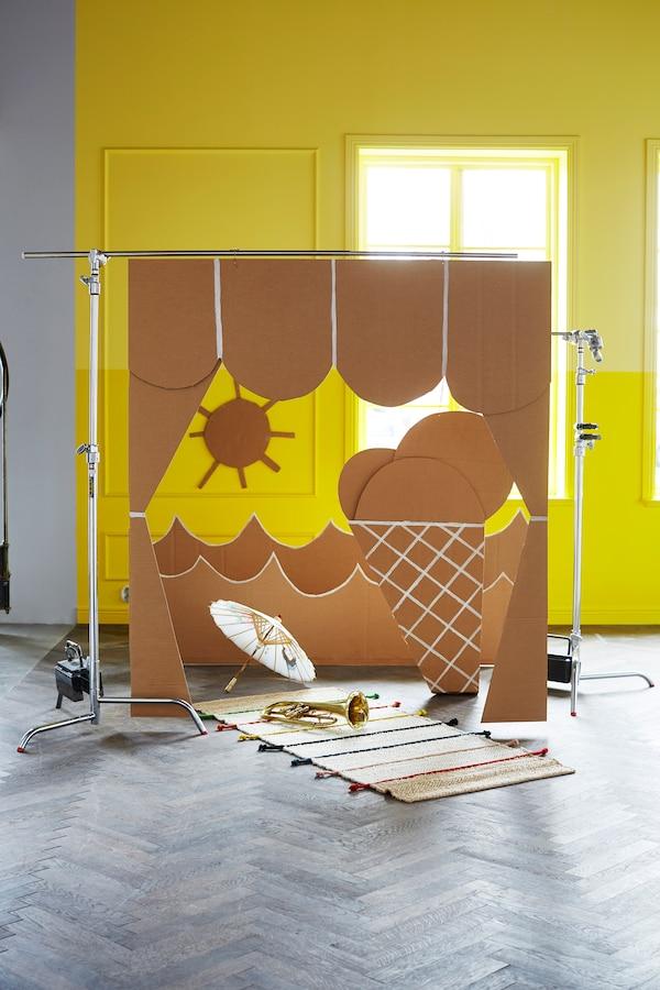 Eine Theaterbühne für Kinder aus Karton, darunter u. a. der flach gewebte in Handarbeit erstellte TILST Teppich in Natur/Bunt