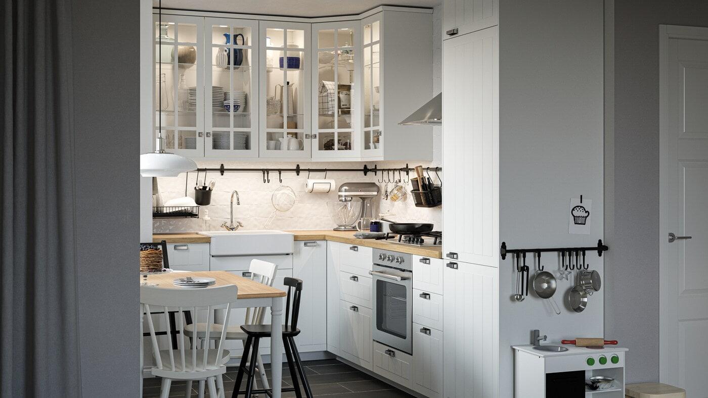 Eine traditionelle Küche mit weißen STENSUND Fronten und Schränken mit Glastüren, u. a. mit einem Esstisch, Stühlen und einer Spielküche.