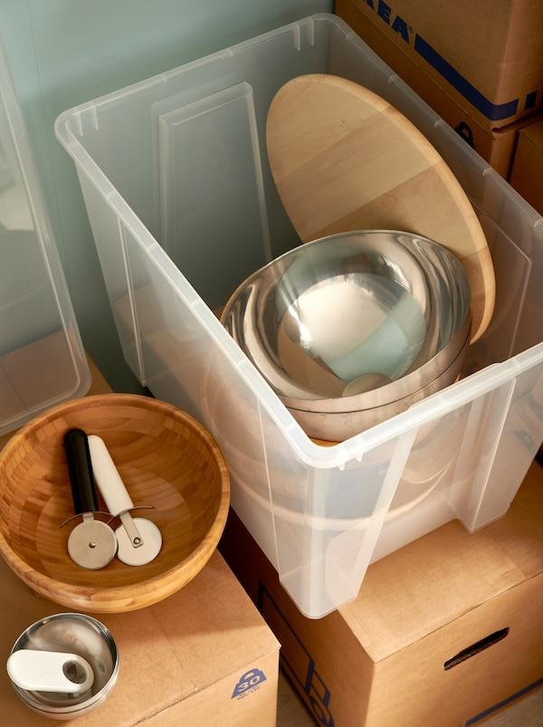Eine transparente SAMLA Box aus Kunststoff, die mit BLANDA Servierschüsseln, einer Drehplatte und Geschirr gefüllt ist, steht auf gestapelten JÄTTENE Umzugskartons.